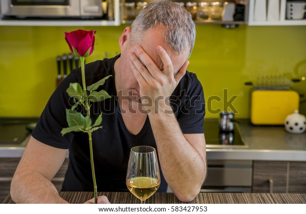 Attractive man with flowers in his hand is waiting. The thoughtful man in kitchen, waits for the woman. She is not coming. Depressed young man holding single rose