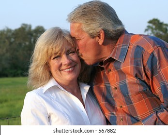 an attractive man giving his beautiful wife a kiss on the cheek