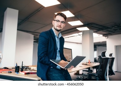 Attractive man in glasses is sitting near the workplace in office. He wears  blue shirt, dark jacket.  He holds laptop and looks to the camera.