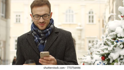 Attractive man in glasses walking happily in the winter town street with coffee in hand and taping on his smartphone. Christmas trees on the background. Outdoor
