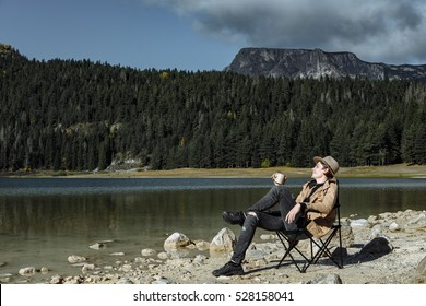 Attractive man in the hat is drinking coffee and enjoying the view of Autumn Black Lake, Durmitor National Park, Zabljak, Montenegro