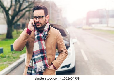 Attractive man having trouble with a car in the street