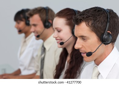 Attractive man with a headset on working in a call center with more people
