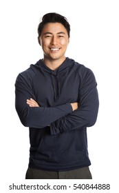 An attractive man in his 20s standing against a white background wearing a blue hood shirt smiling, looking at camera.