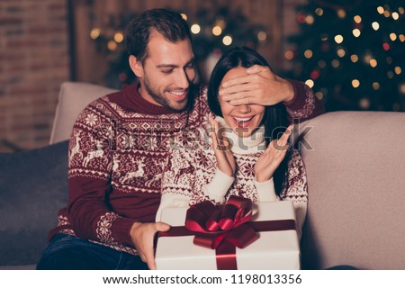 Attractive man hold big white package with red bow sit in cozy living room with illumination garland decorations on pine three close eyes to his brunette lady make surprise