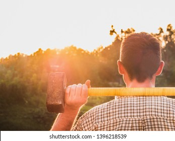 Attractive man holding a sledgehammer in his hands and looking into the distance against a background of trees, blue sky and the rays of the setting sun. National holiday concept