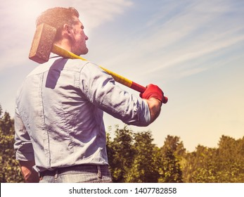 Attractive man holding a sledgehammer and a US Flag in his hands and looking into the distance against a background of trees, blue sky and the rays of the setting sun. National holiday concept