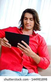 attractive man holding tablet and sitting on sofa in his home
