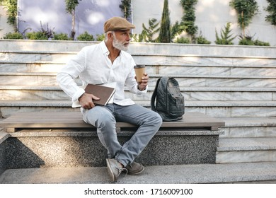 Attractive man holds coffee cup and notebooks. Gray-haired handsome adult guy in white shirt and light jeans is sitting on bench..