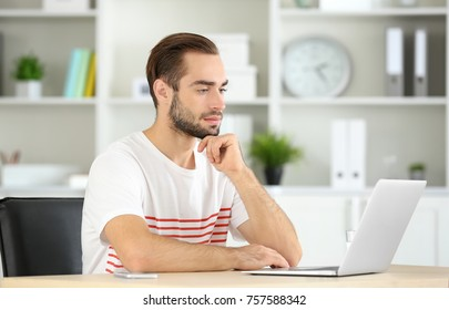 Attractive man with laptop in office