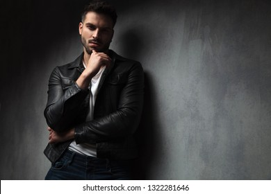attractive man in leather jacket with finger on his chin is thinking while standing against grey studio wall