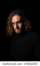 attractive man with long hair with blue eyes looking at camera on black background