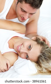 Attractive man looking at his girlfrined lying in bed