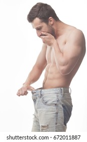 Attractive man is looking in his jeans - impotence concept