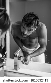 attractive man in the morning in the bathroom brushes his teeth washes his face, morning rituals.