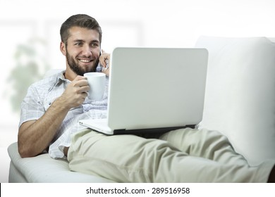 Attractive man with a note book and a coffee cup is talking on a smart phone