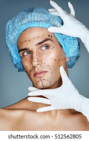 Attractive man patient with guideline marks on his face for plastic surgery operation. Surgeon touching man face. Aesthetic Cosmetology concept