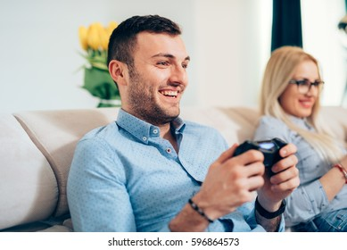 Attractive man playing videogames  with wife or girlfriend on general console.