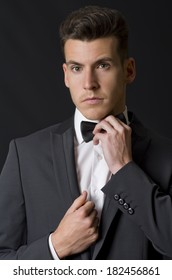 Attractive man posing on black adjusting bow tie