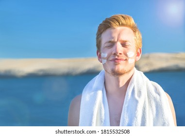 Attractive man with protective sun cream (solar cream, sunscreen ) on the face. Young handsome caucasian male model with red hair on the natural background. Outdoor.
