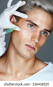 Attractive man receiving botox injection in the area around the eyes. Doctor makes cosmetic injection. Beauty treatment.