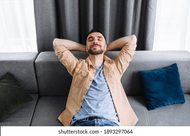 Attractive man is relaxing on the couch in living room at home and smiling. Caucasian stylish guy takes a break from online work, or have weekend, dreaming about vacations