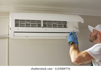 An attractive man repairs the air conditioner.  Fresh air. Comfort temperature. Clear atmosphere. Cooling air. Room heating. Air conditioner repair. Broken air conditioner.