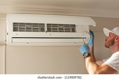 An attractive man repairs the air conditioner.   Fresh air. Comfort temperature. Clear atmosphere. Cooling air. Room heating. Air conditioner repair. Broken conditioner. Dirty filter.