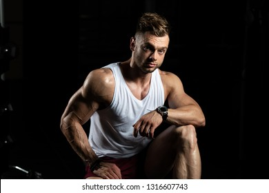 Attractive Man Resting On Bench After Exercise In Fitness Center