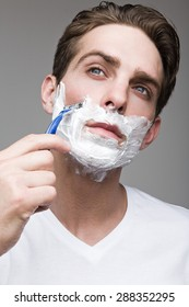 Attractive man shaves