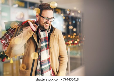 Attractive man shopping holiday presents and smiling