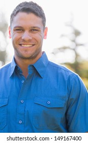 Attractive man with short hair and a blue shirt looks at the camera
