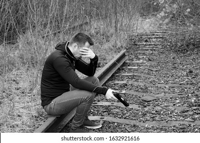 attractive man sitting on rails and holding gun