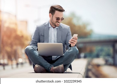 Attractive man sitting outside, using mobile phone and laptop ,looking down while sitting with legs crossed.