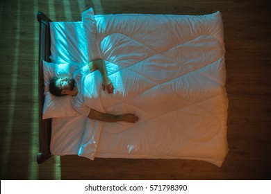 The attractive man sleeping on the bed at night. View from above