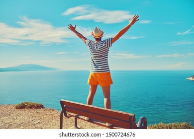 Attractive man standing on the bench and enjoying on the tropical beach. Summer concept.