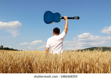 attractive man standing in rye field and holding guitar above head