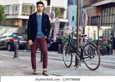 Attractive man in the street wearing british elegant suit near a vintage bicycle. Young bearded businessman with modern hairstyle in urban background.