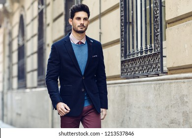 Attractive man in the street wearing british elegant suit. Young bearded businessman with modern hairstyle in urban background.
