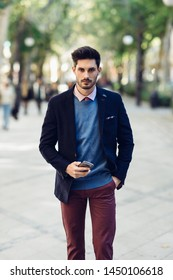 Attractive man in the street wearing british elegant suit with smart phone in his hand. Young bearded businessman with modern hairstyle in urban background.