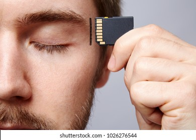 Attractive man at studio background, business concept, copy space, portrait, holding memory card, closed eyes.
