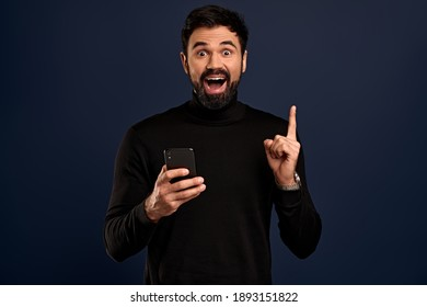 Attractive man in stylish high neck sweater, raise index finger in eureka gesture smiling joyfully, found answer, give interesting suggestion, happy finally solve proble, Pacific Blue background.