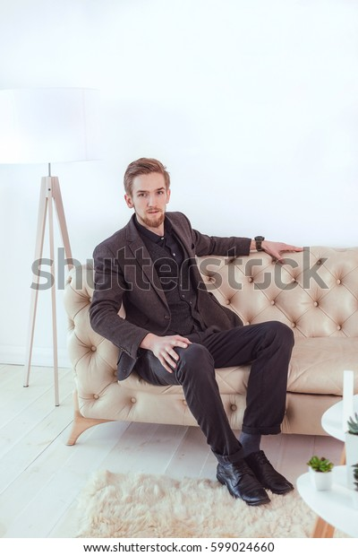 Attractive man in a suit sitting on a sofa