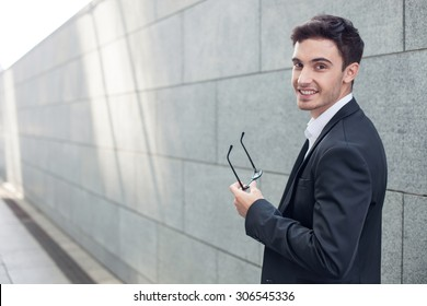 Attractive man in suit is standing and holding eyeglasses in his hand. He is looking forward and smiling. Copy space in left side