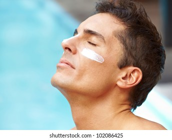 Attractive man sunbathing near pool with sunscreen on his face
