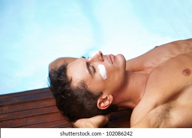 Attractive man sunbathing with sunscreen on his face near pool