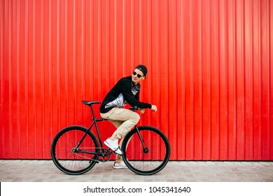 Attractive man in sunglasses, sitting on professional bike, riding, looking back, wearing fashionable clothes and cap. Outside.