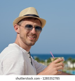 Attractive man in sunhat and sunglasses with long drink cocktail in his hands, he is celebrating an important event, enjoying his holidays and smiling to the camera.