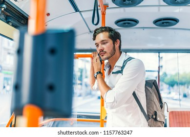 Attractive man talking on the phone in public bus. Man traveling in a bus. Cheerful businessman on a bus. People, lifestyle, travel and public transport.
