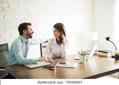 Attractive man touching his female coworker's hand and having a romantic office fling